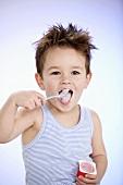 Small boy eating fruit yoghurt