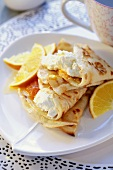 Pancakes with soft cheese and oranges