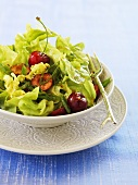 Oak leaf lettuce with fresh cherries and curry dressing