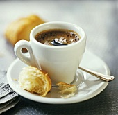 A cup of espresso with a croissant