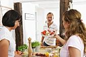 Junge Frau überreicht jungem Mann Tarteform mit Gemüse