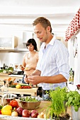 Young couple preparing vegetables in kitchen