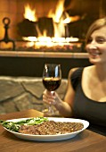 Young woman with rib steak & red wine in front of open fire
