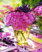 Pink hydrangeas with bunch of lavender in glass vase