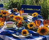 Garland of sunflowers and tea things on garden table