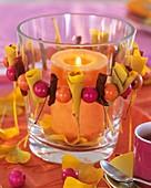Windlicht mit Kranz aus Ginkgo- und Apfelblättern und Holzperlen