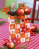 Gift bag with oil bottle, apples, Douglas fir and stars