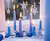 Tablett mit blauen Stabkerzen, Baumkugeln, Sternen am Fenster