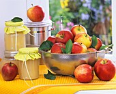 Apples in metal sieve, jars of apple puree