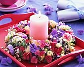 Blütenkranz um rosa Kerze auf einem Tablett