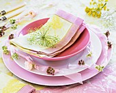 Place-setting in shades of pink with flowering herbs & napkin