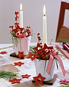 Gestecke mit Ilex-Beeren, Kiefer, roten Sternen und Kerzen