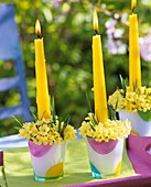 Glasses filled with cowslips & grasses used as candle holders