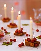Sternförmiger Kerzenhalter mit Zieräpfeln und weisser Kerze