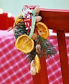 Weihnachtliches Gesteck hängt an roter Stuhllehne