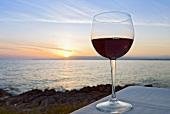Ein Glas Rotwein vor Sonnenuntergang am See
