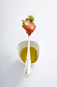Tomato and basil on fork over small dish of olive oil