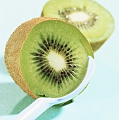 A kiwi fruit, cut open, with a spoon