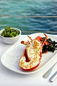 Grilled lobster with saffron on table by sea