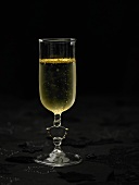 A glass of sparkling wine with gold leaf