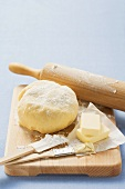 Ball of dough, butter and baking utensils on wooden board
