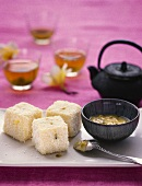 Lamingtons (cubes of white chocolate cake) with passion fruit sauce, tea