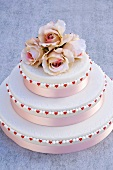 Three-tiered wedding cake with pink roses