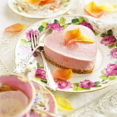 Heart-shaped pink cheesecake with rose petals