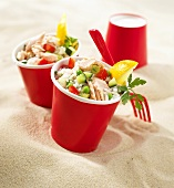 Rice salad with salmon and vegetables in red paper cups