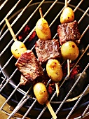Beef and potato skewers on a barbecue