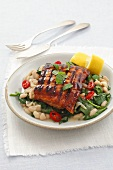 Glazed grilled salmon fillet with spinach and white beans