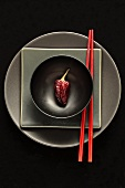 Dried chilli in black bowl on plates with chopsticks
