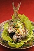 Fish with julienne vegetables on lettuce leaf (China)