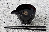Small bowl of soy sauce and chopsticks on rice