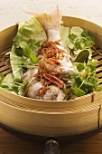 Steamed fish with fresh coriander in bamboo basket (Asia)