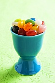 Coloured jelly beans in an egg cup