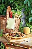 Vegetable pizza, melon and basket with grissini and herbs