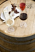 Glasses of wine, cheese platter and grapes on wine barrel