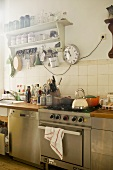 Kitchen counter with stainless steel cooker and dishwasher, station clock next to vintage shelving