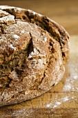 Fresh farmhouse bread on wooden table with flour