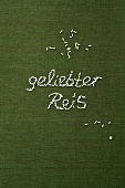 The words 'geliebter Reis' ('beloved rice') written in grains of rice