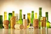 Various wine bottle closures, wine bottles in background