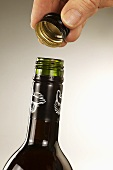 Opening bottle of red wine with metal screw-top cap