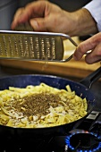 Grating truffle over ribbon pasta