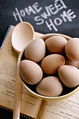 Fresh eggs in bowl on cookery book with wooden spoon