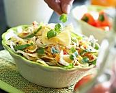 Garnishing pasta salad with basil