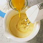 Making cake mixture: mixing oil with juice