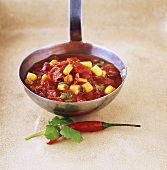 Tomato sauce with chili and sweetcorn on ladle