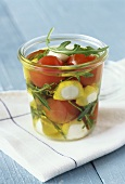 Marinated cherry tomatoes with mozzarella and rocket in jar
