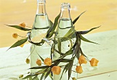 Summer table decoration: bottles of water with flower garland